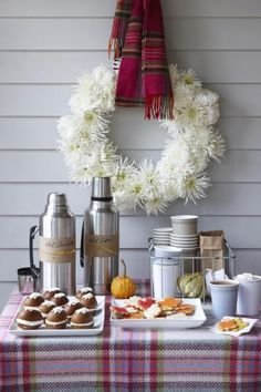 What a cozy scene! This wreath of pure white flowers is hung with a plaid flannel scarf over a table of cookies and hot cocoa. | 12 of our favorite wreaths | Living the Country Life | http://www.livingthecountrylife.com/homes-acreages/country-homes/12-our-favorite-wreaths/