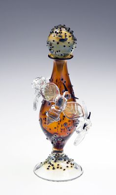 Bee Bottle by Loy Allen. *Lampworked:lampwork* bees, their wings dusted with shimmering *dichroic:dichroism* glass, perch on the a lampworked perfume bottle accented with black *frit*.