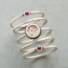 PAINTED PLUM BLOSSOM RING SET--Ananda Khalsa transforms a petite painting into wearable art, framing it on one of five sterling silver bands. Two others graced with a rose cut ruby. Ring set handmade in USA. Whole sizes 5 to 9.