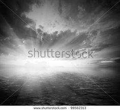 black and white dramatic landscape with water with waves and cloudy sky at sunset - stock photo
