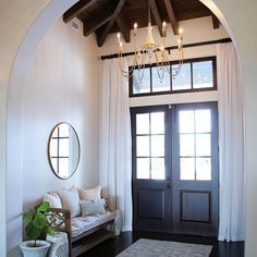 Arched Foyer with Double Wood Front Doors with draperies, Chandelier, Bench, Dark Hardwood floors and exposed ceiling beams. Bench and chandelier is Gabby Decor. Mirror is by Wisteria.
