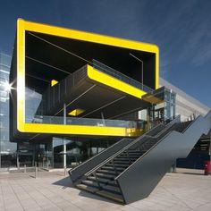 ExCel Phase II par Grimshaw.  Architectes britanniques Grimshaw ont achevé une extension au palais des congrès d'Excel à Londres avec une entrée en forme de E et de couleur jaune vif. La spirale jaune est destinée à augmenter la visibilité de l'entrée , mettant en évidence l'accès aux différents niveaux et fournissant un parcours clair pour les visiteurs.