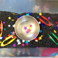 Space themed sensory table with black beans, star buttons from Joanne's Fabric Store, kids tweezers and a bowl for sorting. Great for sensory, fine motor, and social development.