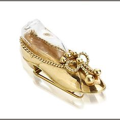An eighteen karat gold brooch, Paul Flato. Brooch in the form of a slipper with rope-twist bow detail and glass insert; unsigned, attributed to Paul Flato; length: 1 3/4in.