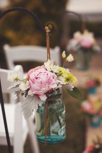 Mason jars as flower vases. You could hang these from trees to and alternate between flowers and candles. You could do the same thing on the tables using larger size jars for the flowers and smaller ones for the floating candles.