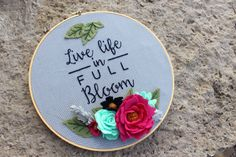 Live life in full bloom Fill your home with positivity and sunshine with this gorgeous handcrafted floral embroidery hoop. Hand embroidered on grey