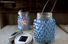 Set the mood with a DIY glass pebble lantern! Colored stones, glue and a solar jar lid makes it easy.
