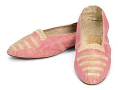 Pair of lady's pumps, 1790s. Pink glacé kid, shashed to reveal ivory silk, trimmed wiht ruched silk ribbons. With paper label in one insole: Scott, London Boot & Shoe Maker, Leicester Square, Mrs Kennedy Gough (?).