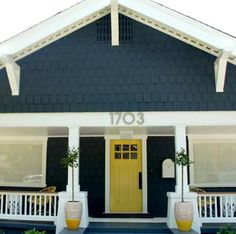 Steel-blue wood, crisp white trim and a yellow door that just pops.