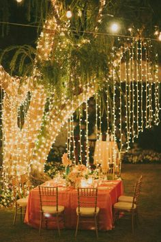 Now this is what I call 'Fine Dining'. Gorgeous dangling fairy lights around an outside table setting.