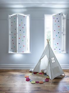 A fun and playful idea for a children's bedroom or nursery. These solid white shutters have colourful polka dot stickers dotted all over them. A simple home decor DIY that is a great solution for nursery window dressing