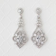 Beautifully styled with vintage flair, these bridal earrings are designed with tapered baguettes, oval cut and pear cut jewels. A radiant design for weddings, homecoming, prom or any other event! Pierced post backs and 2 inches long. Rhodium plated or gold plated, grade AAA cubic zirconia and lead free.