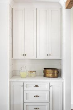 Cute little pantry corner displays white shiplap backsplash walls, white shaker cabinets and dark nickel oval knobs and cup pulls.