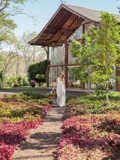 Casa tem paredes de vidro para que a área externa integre o ambiente e dar destaque a cachoeira perto dessa casa de campo.