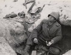 January 7, 1945, T/Sgt. Lawrence J. Gettings of Owtumwa, Iowa, experiences the full luxury of winter foxhole life southeast of Bastogne, 320th Infantry Regiment, 35th Infantry Division.