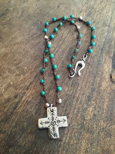 Beautiful turquoise and detailed pewter beads are crocheted onto dark brown nylon cord featuring an artisan cross pendant. Love this boho look and style, sure to become your go-to piece to accessorize with. Dress it up or down, this necklace goes with just about anything!  Measures: Approx. 18 inches in length (not including pendant) pendant measures 1 inches in length.  I only use top quality beads in my work.  Thanks for visiting...