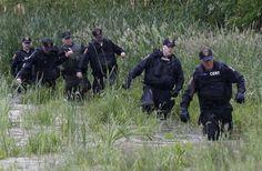 Law enforcement officers walk in water while searching a field near Willsboro, New York June 9, 2015. - © REUTERS/Chris Wattie