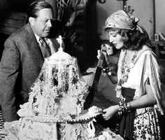 Dressed in a costume from The Firefly, Jeanette MacDonald begins slicing her birthday cake. First in line is director Robert Z. Leonard.