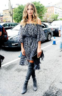 Hannah Davis wears a printed off-the-shoulder dress, thigh-high boots, and a fringe clutch