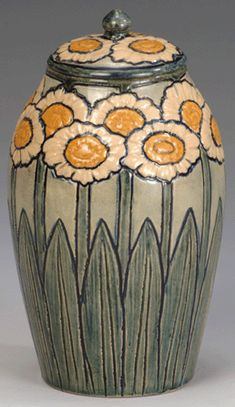 "Newcomb Pottery, lidded jar with a design of stylized daisies, 1903. Designed and executed by Harriet ""Hattie"" Coulter Joor; potted by Joseph Fortune Meyer. Glazed earthenware, height 7¾ inches."