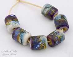 Handmade lampwork beads by Judith Billig. Colorful and organic glass beads in green, ivory and purple. Judithbillig.com