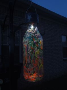 """July 4th solar lights on clearance for 50 cents. Removed the solar top and glued it to a snapple bottle that was """"painted"""" on the inside. Added a piece of wire so that it can hang anywhere."""