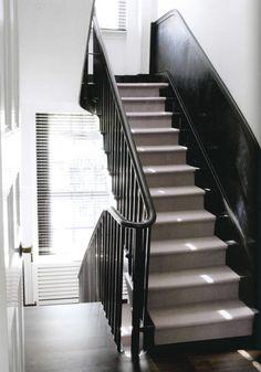 Mooie zwarte trap en geschilderde lambrisering met loper.