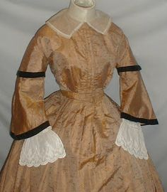 A stunning 1860's gold silk dress that has been de-accessioned from the Metropolitan Museum of Art. The fabric has a darker gold sprig pattern.  Full pagoda  sleeves w/wide sleeve cap. Sleeves trimmed with bands of black velvet; neck and armscyes are piped. Dress has original organdy attached collar. The under sleeves are not original to the dress.