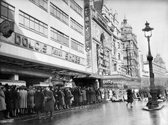 Everyday Life In London, England, A busy scene in London's Leicester Square as civilians and service personnel queue for admission to the Empire and Ritz cinemas. The queue snakes past a large Dolcis shoe shop and a small milk bar before reaching the cinemas. The Empire is showing 'The Philadelphia Story', starring Cary Grant, Katharine Hepburn and James Stewart, whilst the Ritz appears to be showing 'Gone with the Wind'. 1941