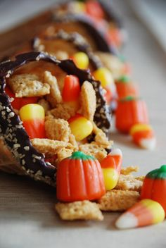 """Candy Cornucopia: Dip top of waffle cone in melted chocolate and sprinkled with gold sugar. Fill with Caramelized Crispy Snack Mix, candy corn and candy pumpkins. Insert the waffle cones into cone-shaped cellophane bags. Tie with raffia. Add a gift tag ~ """"Give Thanks to the Lord for He is good""""!"""