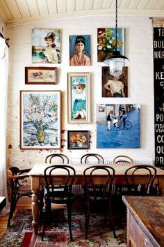 Gallery wall with paintings of people and bright art. Love this eclectic filled art space.