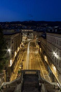 Piazza Goldoni dalla Scala dei Giganti. Trieste Italy | La Scala dei Giganti, situata tra piazza Goldoni e via del Monte, è un'imponente e ripida scalinata che permette di collegare il cuore pulsante della città con le sue vie di comunicazione, i negozi e i locali del centro, al colle di San Giusto, con il suo complesso archeologico. Fu costruita nel 1907 grazie ad un progetto dei Berlam, una nota famiglia di architetti triestini. In stile neoclassico, la Scala dei...