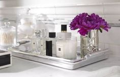 Keep your bathroom neat by using a tray to contain cosmetics, perfumes, and flowers for display- image via Urrutia Design