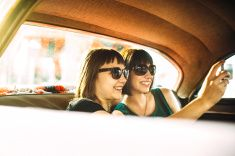 Attractive Young Women Take Selfie With Smartphone In Vintage Car stock photo