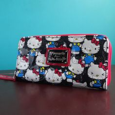 Zip-around wallet with vintage Hello Kitty print on signature Loungefly embossed patent leather material. White polyester inside lining, 2 bill slots, 1 ID slot, 4 card slots, and 1 zippered coin pock