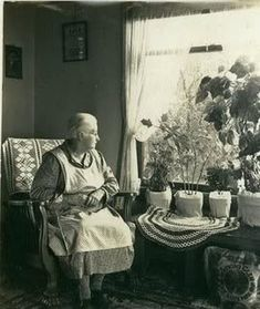 The history of aprons. the photo doesn't really look like my Grandma, but she wore an apron like that, dresses like that, had her chair by the window and plants filling a table in front of it like that.I miss my Grandma. Vintage Pictures, Old Pictures, Old Photos, Grandma Moses, Aprons Vintage, Look Vintage, Vintage Linen, The Good Old Days, Vintage Photographs