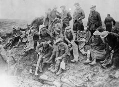 Soldiers of the Gordon Highlanders putting on rubber thigh boots, Bazentin-le-Petit, November 1916.