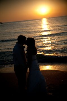 A kiss before sunset shared between one of our Florida beach wedding couples