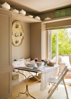Office con banco, balda y armarios a medida. Office con un banco con cojines y una silla junto a la puerta que comunica con la terraza