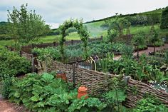 Kitchen vegetable garden enclosed by a wattle fence and bordered by rhubarb jardin potager bauerngarten Potager Garden, Veg Garden, Garden Cottage, Edible Garden, Garden Landscaping, Permaculture Garden, Garden Stakes, Lush Garden, Gardening Tools