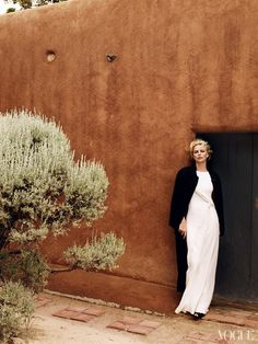 The austere elegance of a wool crepe coat tossed over a silk column suits the rustic simplicity of O\'Keeffe\'s winter compound in Abiquiu, New Mexico. Calvin Klein Collection trench and stretch silk-crepe dress with plissé detail.