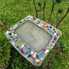 A trash can lid was used as a concrete form for the base of this birdbath. (The middle indentation comes from the top of a water cooler that was pressed into the wet concrete.) Broken pieces of colored glass and pottery create a decorativemosaic effect along the edges.