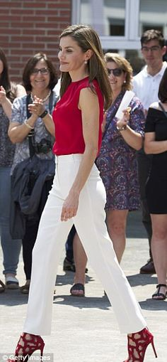 Red was the colour for Queen Letizia of Spain today as she donned a satin top and lattice sandals from high street favourite Mango to visit schoolchildren taking part in a cultural programme.