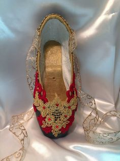 Beautiful, custom designed gold and red appliqués with red Swarovski crystals give this beautiful pointe shoe a decidedly Spanish feel. The shoe