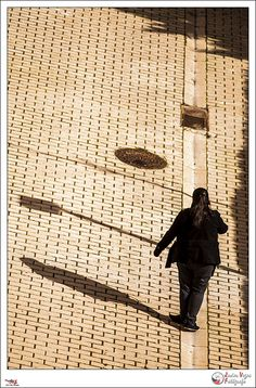 Sombras paralelas - p365jvr - 26 de febrero de 2013. 57/365  Otra vez desde la ventana. Esta mañana hacía un sol impresionante y por eso decidí sacar la cámara. En principio estaba buscando algún gato, como el de ayer, pero ni rastro. De repente giro la cámara y veo a esta chica caminando en línea recta siguiendo la línea marcada por el caz con la suerte de tener una luz que proyectaban unas sombras alargadas.