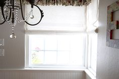 Designer Michaela Warner added softness and style to this breakfast nook with Laura Ashley Flat Roman Shades.