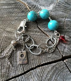"'Hope' -  ""HOPE Shines Brightest in The Darkest Moments, NEVER GIVE UP""  Hope is more powerful than fear, face your fears and never give up...   Three beautiful turquoise gemstones, a red crystal, silver chain and HOPE.  $18"