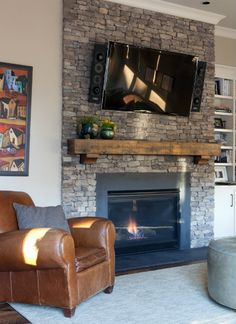 A nice thick wood mantle above this stone fireplace.