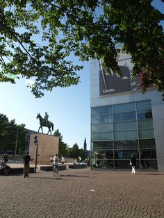 Kiasma contemporary art museum and the satue of marshal Mannerheim with his horse, Mannerheimintie/'Mannerheim street', Helsinki - Nykytaiteen museo Kiasma tekee tunnetuksi nykytaidetta ja vahvistaa sitä olemalla yhteyksissä taiteilijoihin ja yleisöön. Sen toiminta perustuu ajatukseen visuaalisen kulttuurin keskuksesta.Museo toimii kansalaisten kohtaamispaikkana, jonka tarkoituksena on saattaa nykytaide kosketukseen erilaisten yleisöjen kanssa, sekä tuoda oman ajan taide osaksi ihmisten…