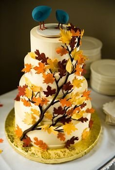 A cascade of fondant leaves in vibrant autumnal hues reflects the season; a bird-themed cake topper in bright teal adds a modern touch.    Cake design by Mike's Amazing Cakes